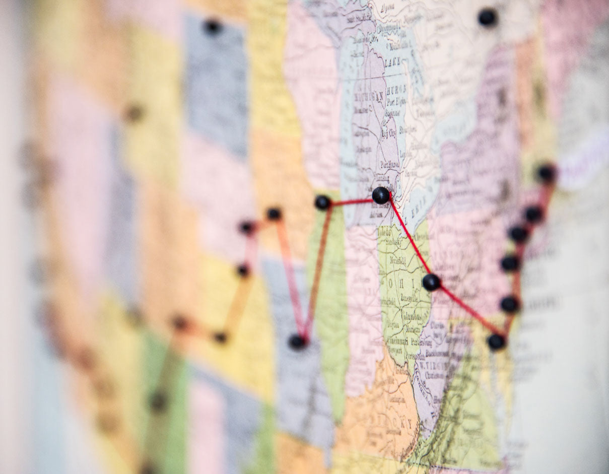Close-up of pushpins and string on a map of the USA charting a road trip