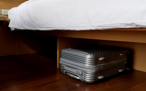 suitcase storing clothes under a bed to prevent damage and bugs