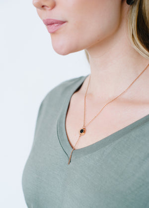 Beck & Boosh Circle of Love Necklace Circle of Love Written Around Black Circle Center Rose Gold Plated On Model