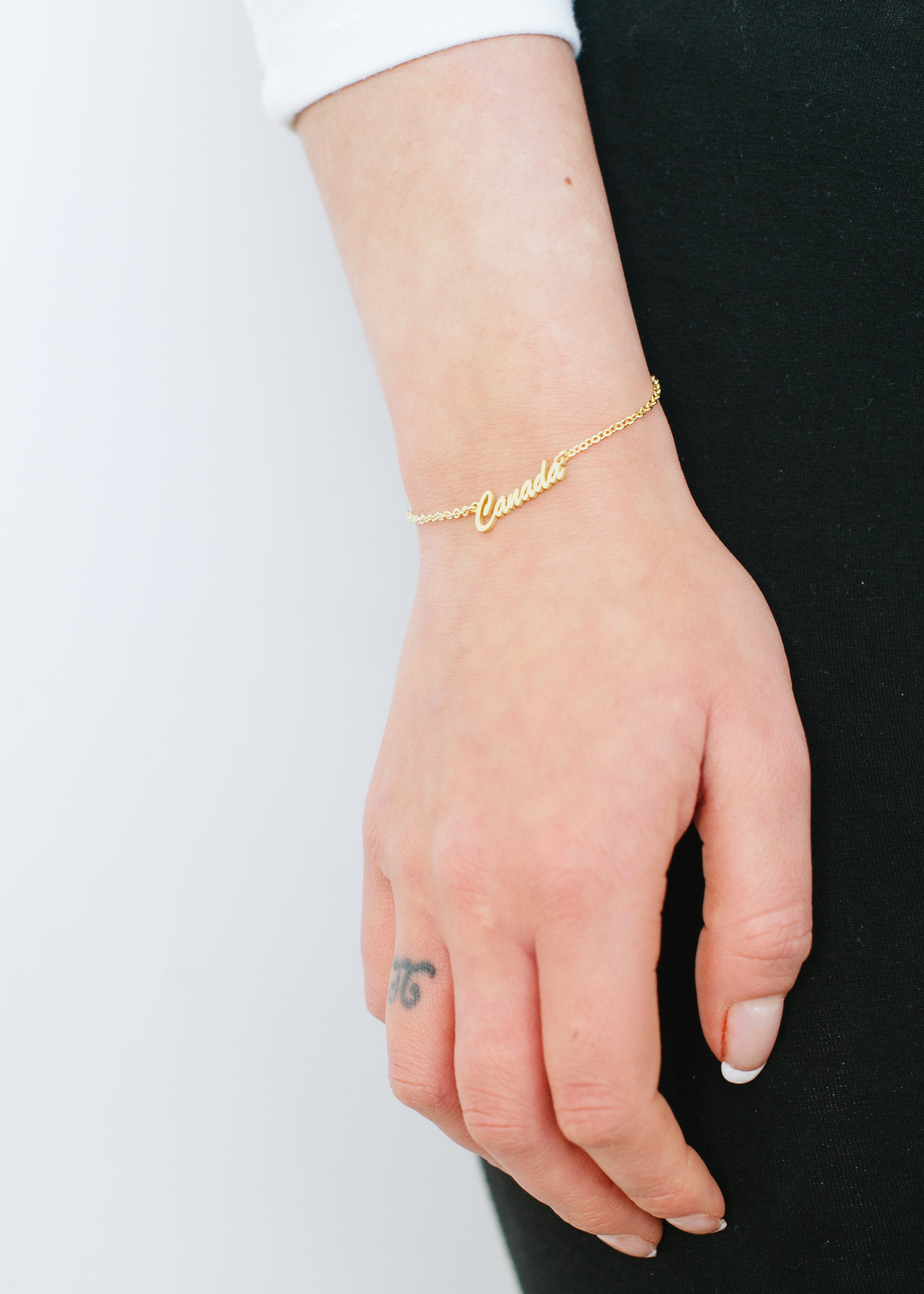 "Beck & Boosh Canada Script Bracelet Simple ""Canada"" written on plated silver chain on model."