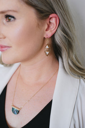 Beck & Boosh Tribal Dangles Plated Gold Oval Pendants with White Marble Triangle Inserts and Crisscross Cut Out in-between On Model