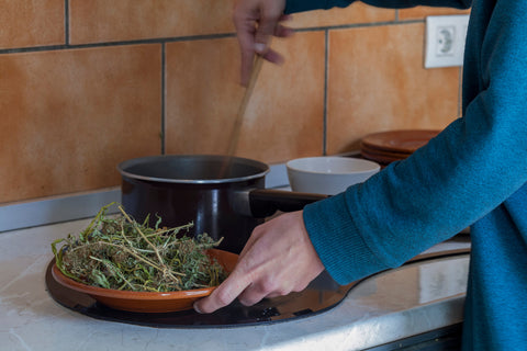 person heating cannabis leaves in a pot