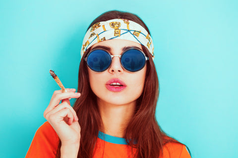 A girl in sunglasses smoking weed.