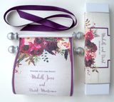 Floral wedding invitation scroll with aubergine and burgundy blooms and aged gold accents, with presentation box