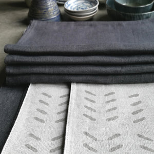 Modern block printed linen placemat set with matching napkins in cool grey stone and dark grey charcoal.