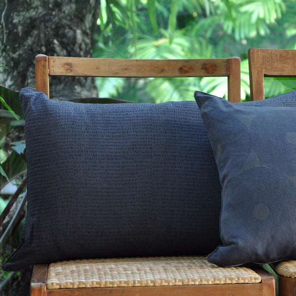 Common Texture square pure linen cushion cover featuring hand block printed drops in indigo blue on dark charcoal grey with contrasting gold zip and leather pull tag.