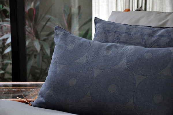 Common Texture Midnight Geometry pure linen cushion cover featuring a hand block printed circle pattern in indigo blue on dark charcoal grey with contrasting gold zip and leather pull tag.