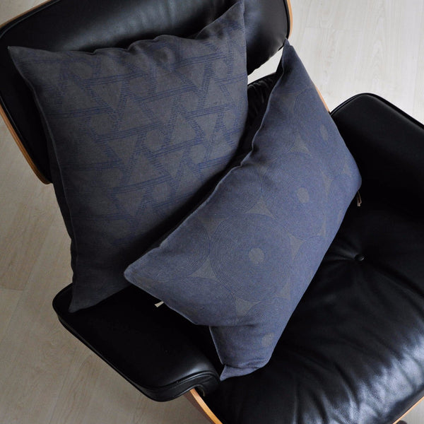 Set of Common Texture pure linen cushions on a chair featuring hand block printed patterns in indigo blue on dark charcoal grey with contrasting gold zip and leather pull tag.