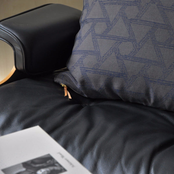 Common Texture square pure linen cushion cover featuring hand block printed triangles in indigo blue on dark charcoal grey with contrasting gold zip and leather pull tag.