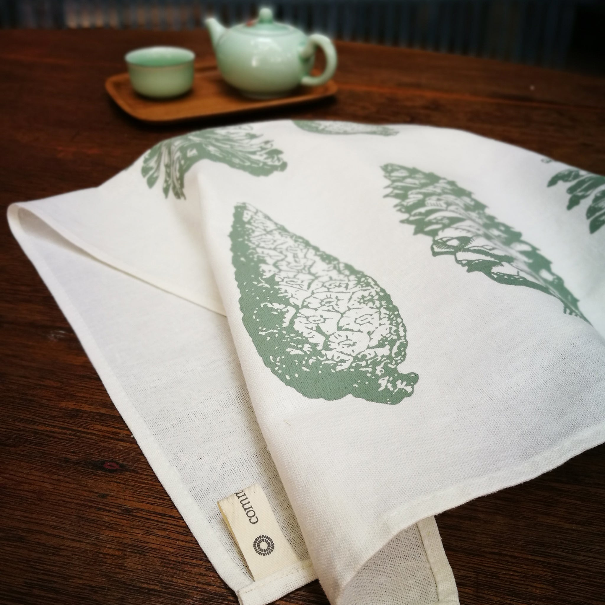 Common Texture kitchen tea dish towels on ecru linen cotton with pine cone botanical print in sage green and misty grey.