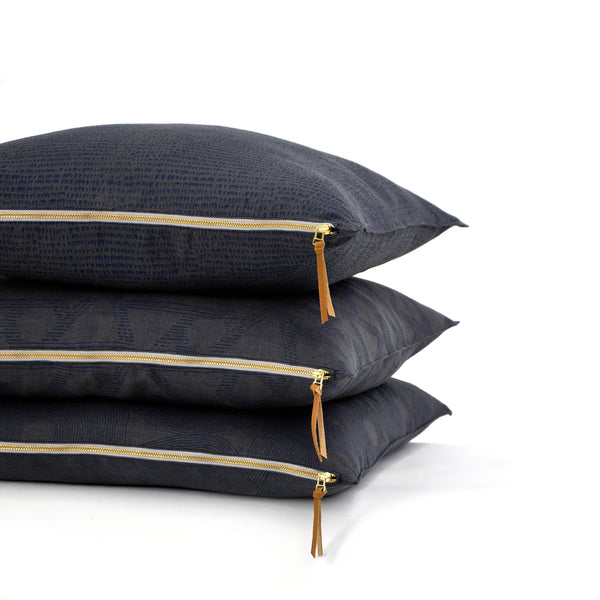 Common Texture Midnight Geometry pure linen cushion covers featuring hand block printed circle patterns in indigo blue on dark charcoal grey with contrasting gold zip and leather pull tag.