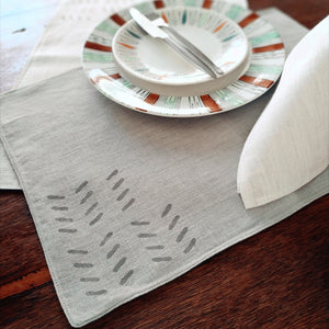 Common Texture hand block printed linen placemat set with matching napkins in cool grey stone, dark grey charcoal and sand ecru.