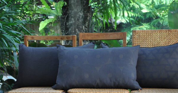 Common Texture lumbar rectangular pure linen cushions featuring hand block printed patterns in indigo blue on dark charcoal grey with gold zip and leather pull tag.