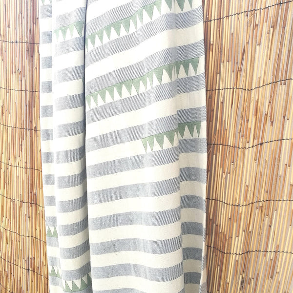 Common Texture extra large summer essential beach towel in pure cotton; off white blue stripes with unique hand block print in sage green. Use at pool, beach, sofa cover up or yoga blanket.