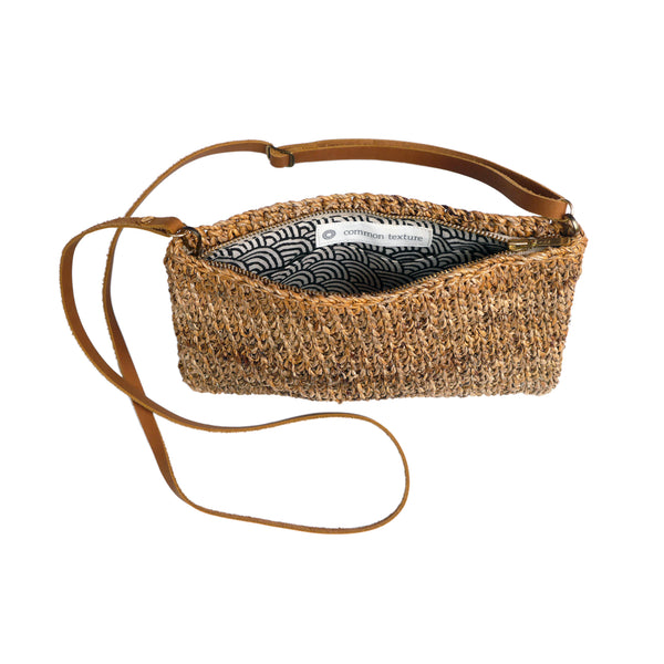 Hand woven crossbody bag made with natural banana fiber featuring zip, divided insert and adjustable leather strap for day or evening.