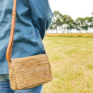 Common Texture handrafted woven sling or crossbody bag made with natural banana fiber featuring zip, divided insert and adjustable leather strap for day or evening.