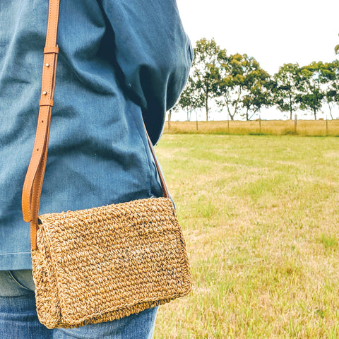 Common Texture woven sling bag handmade with natural banana fiber featuring a fold over flap and adjustable leather strap to wear over the shoulder or across the body.