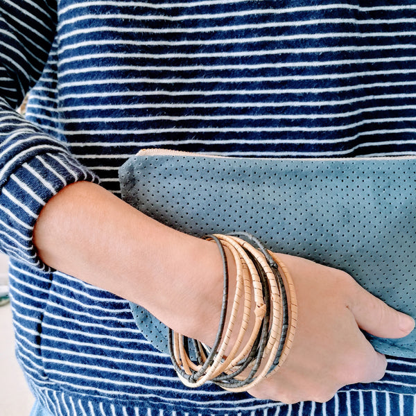 Common Texture set of 12 thin handmade rattan bangles bracelets from Malaysia in natural colors paired with a blue suede purse clutch.