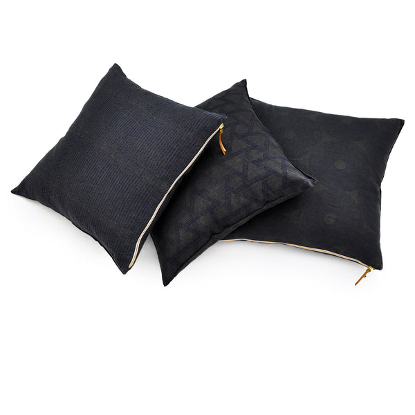 Common Texture Midnight Geometry pure linen cushion covers featuring hand block printed patterns in indigo blue on dark charcoal grey with contrasting gold zip and leather pull tag.