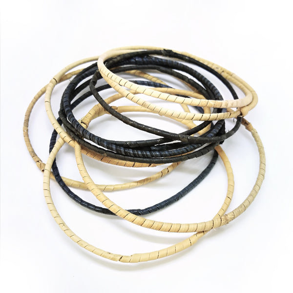 Common Texture set of 12 thin handmade rattan bangles bracelets from Malaysia in natural colors.