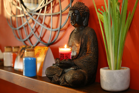 gel candle with buddha and some greens on the shelf abpve the bed - candles for home decor