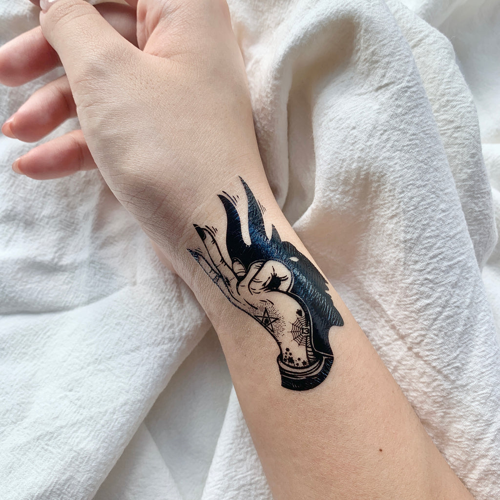 fake small magic hand shadow illustrative temporary tattoo sticker design idea on wrist