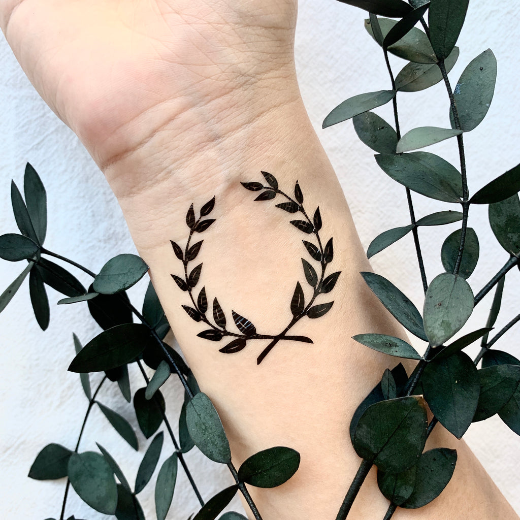 fake small laurel wreath minimalist temporary tattoo sticker design idea on wrist