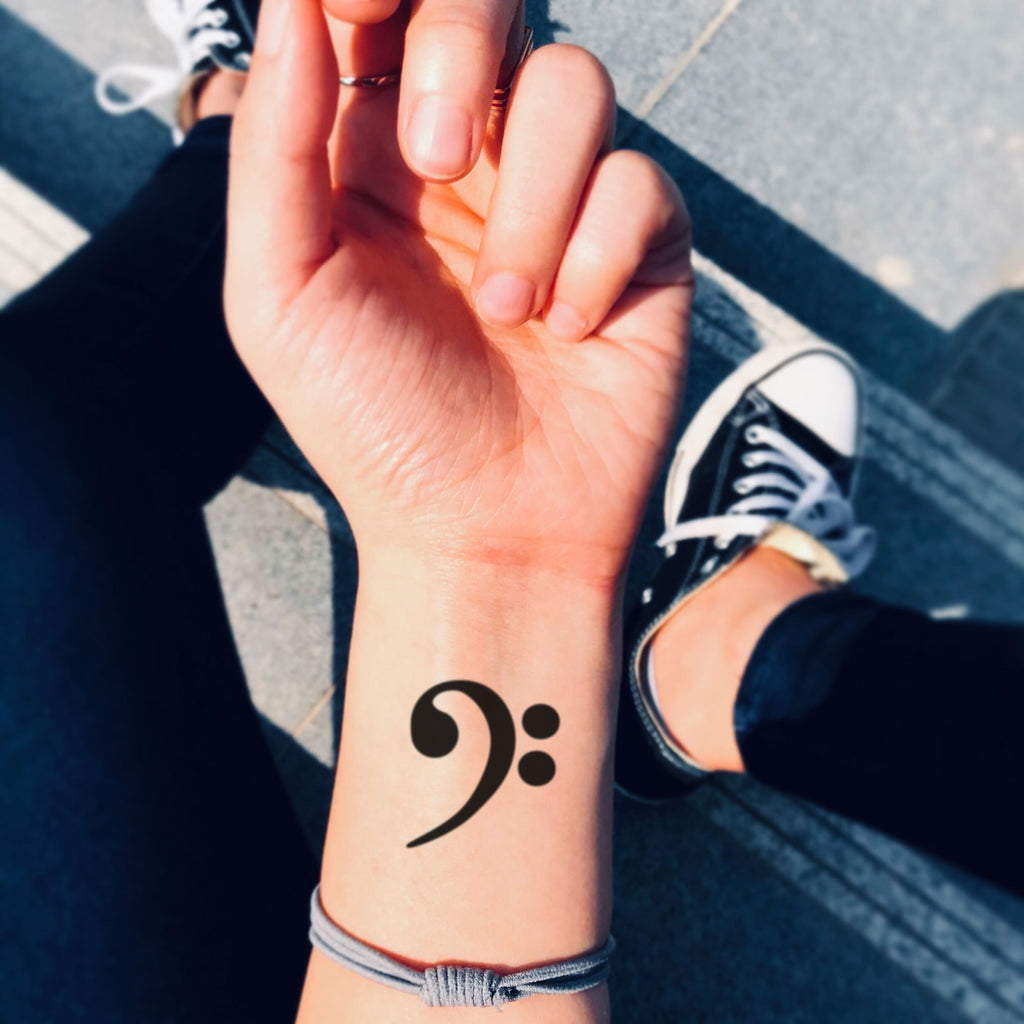 fake small bass clef music temporary tattoo sticker design idea on wrist