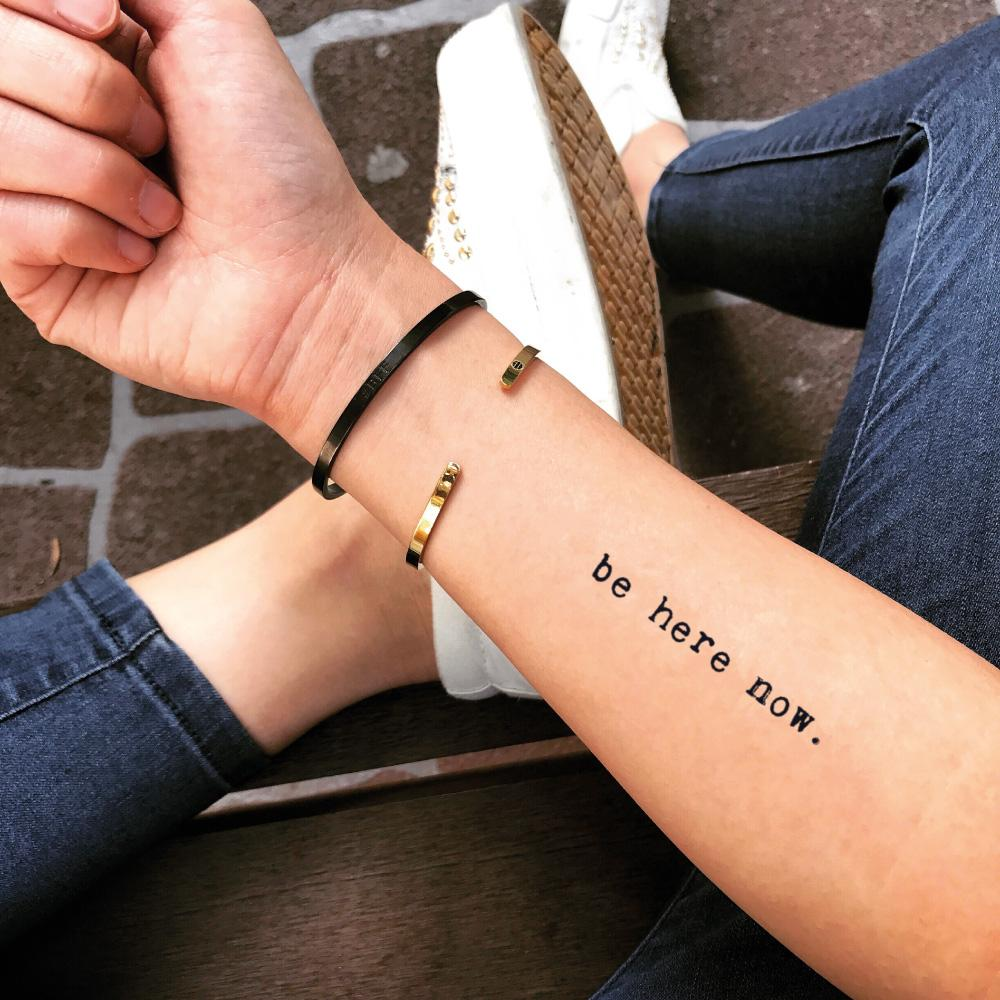 fake small be here now quote lettering temporary tattoo sticker design idea on forearm