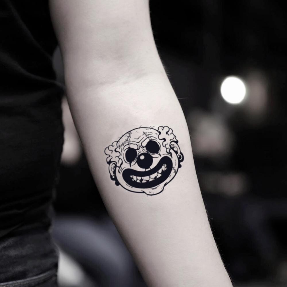 fake small demon evil killer scary clown face cartoon temporary tattoo sticker design idea on inner arm