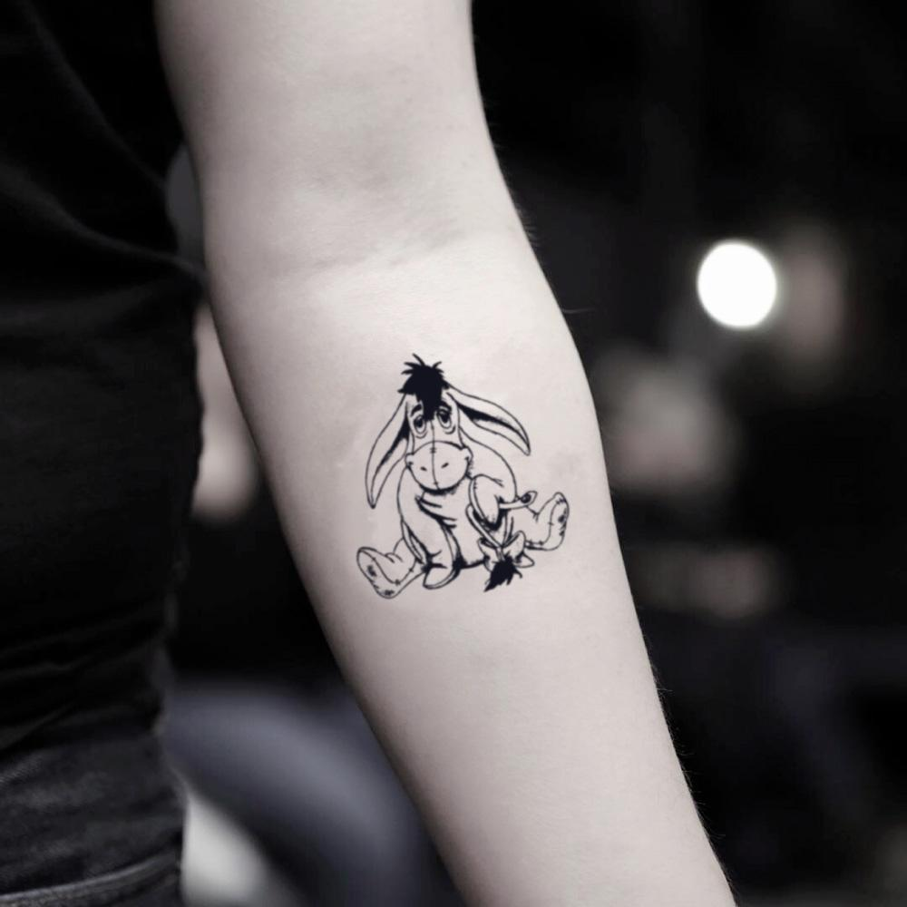 fake small eeyore cartoon temporary tattoo sticker design idea on inner arm