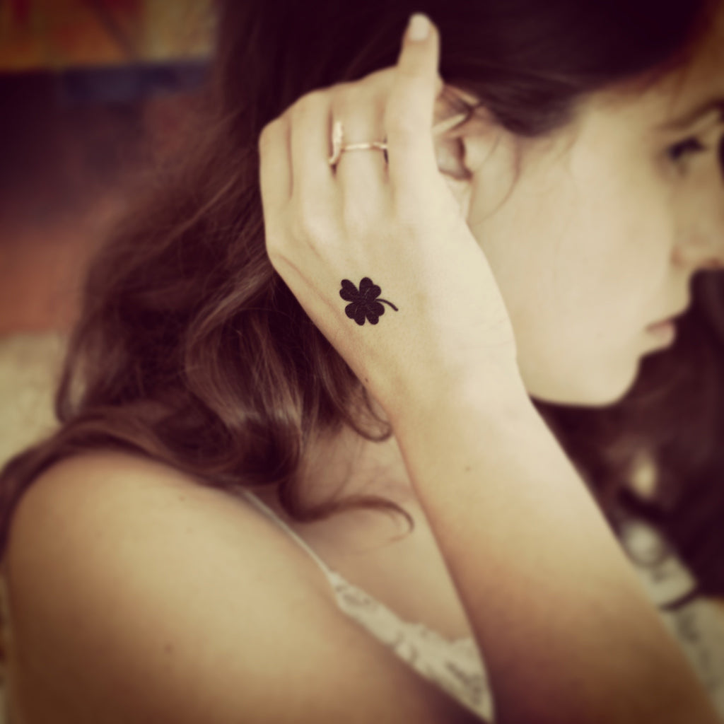 fake small black four leaf clover lucky charm minimalist temporary tattoo sticker design idea on wrist