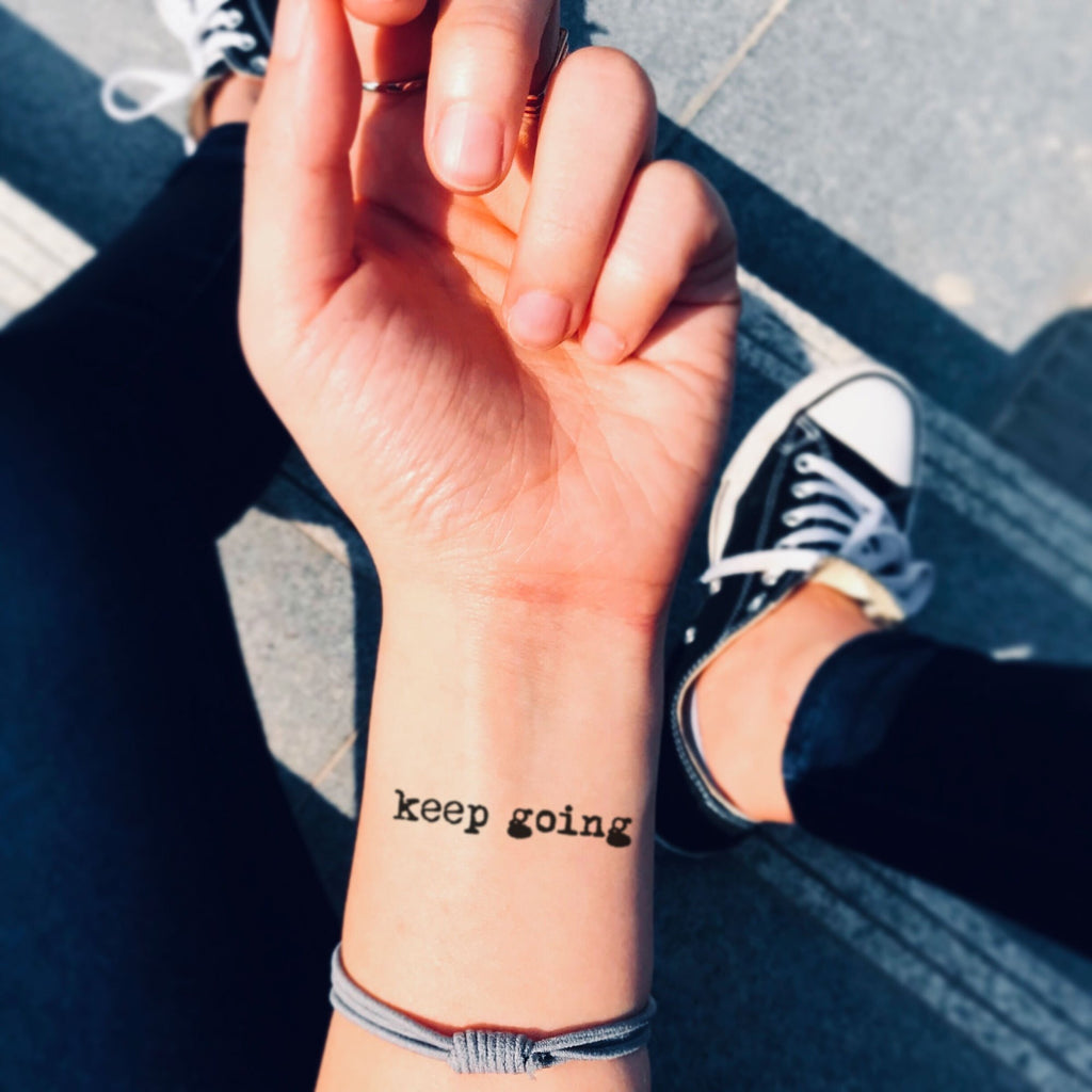 fake small keep going lettering temporary tattoo sticker design idea on wrist