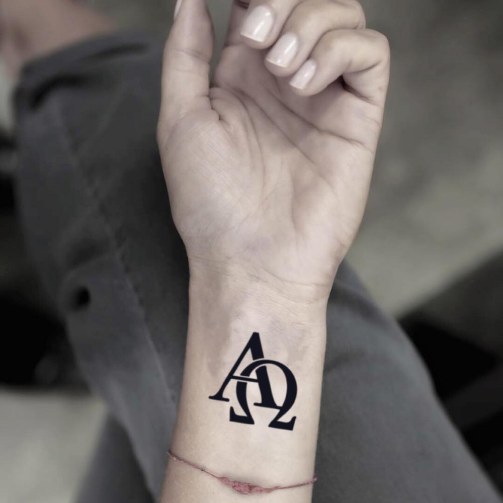 fake small alpha omega lettering temporary tattoo sticker design idea on wrist