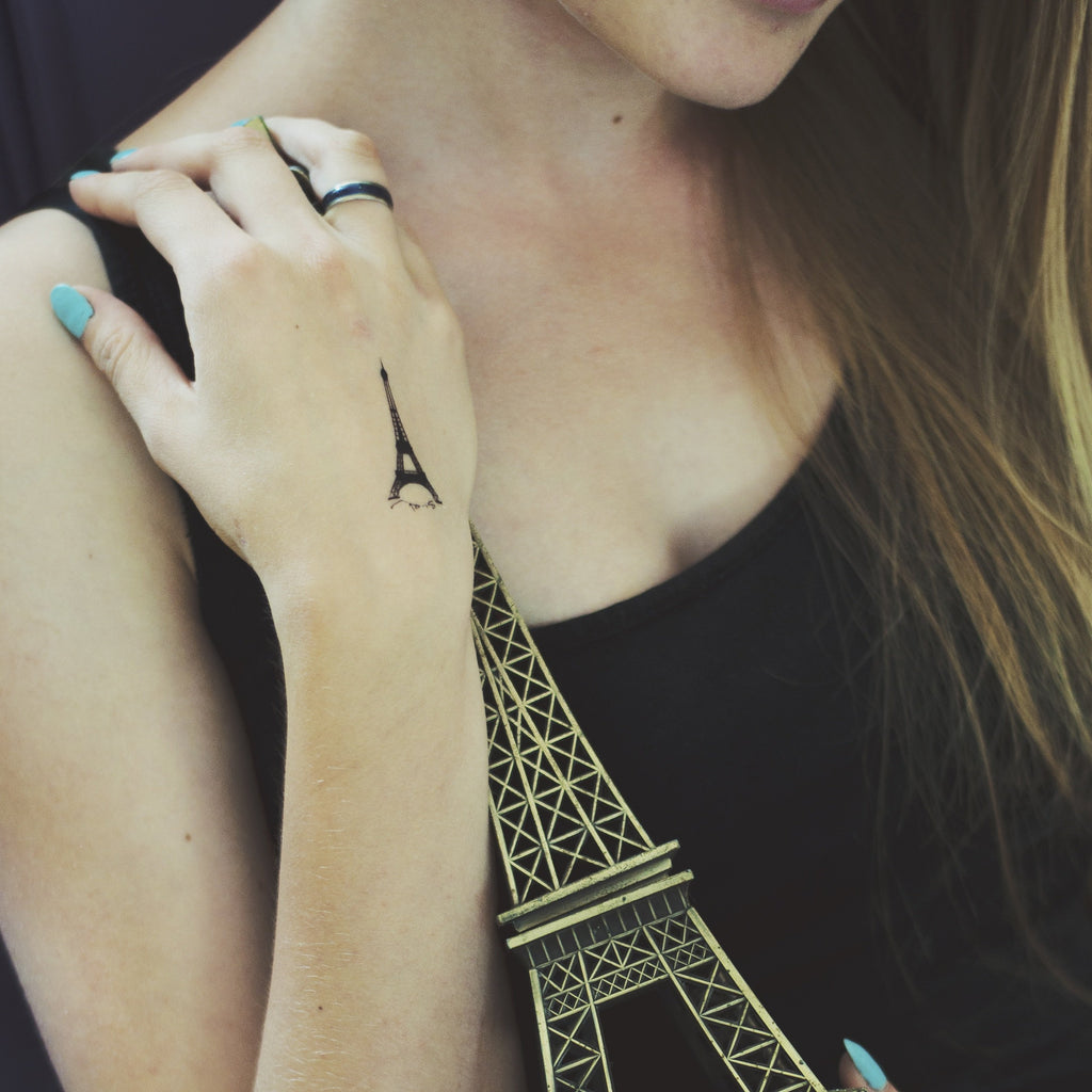 fake small paris eiffel tower illustrative temporary tattoo sticker design idea on wrist