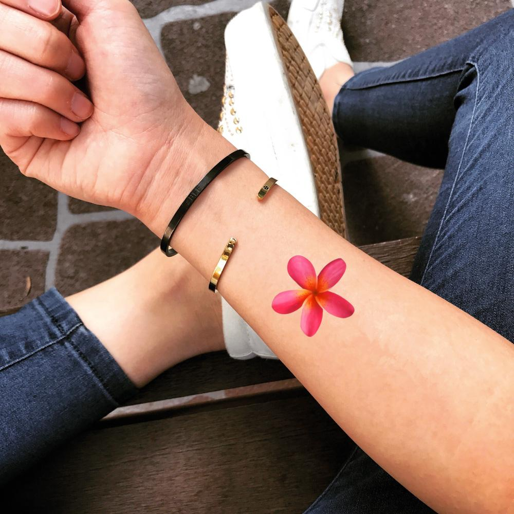 fake small light pink ink plumeria flower color temporary tattoo sticker design idea on wrist