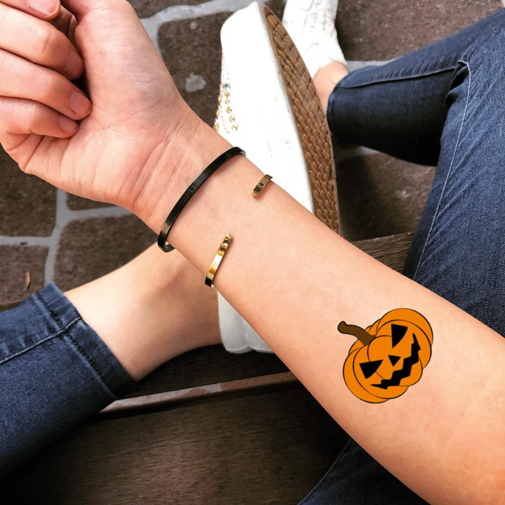 fake small pumpkin jack o lantern halloween color temporary tattoo sticker design idea on forearm