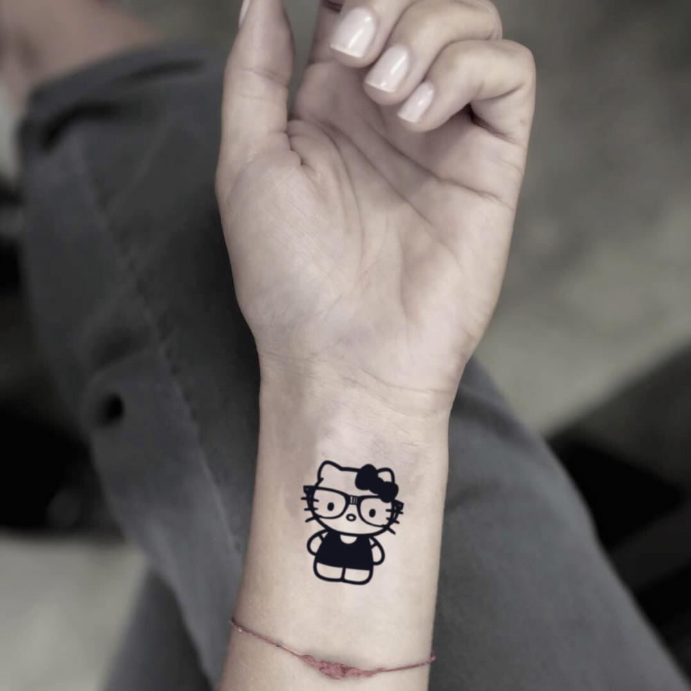 fake small reading hello kitty cartoon temporary tattoo sticker design idea on wrist