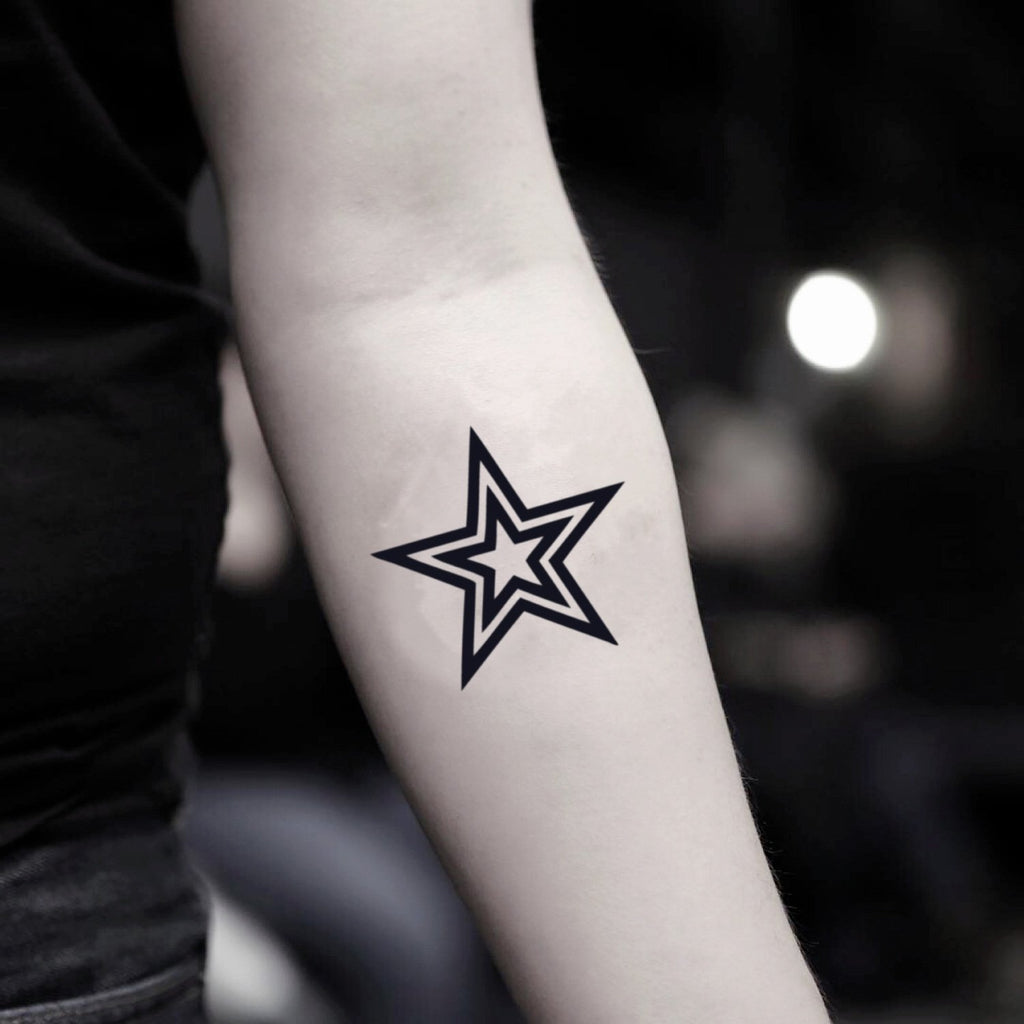 fake small black star outline geometric temporary tattoo sticker design idea on inner arm