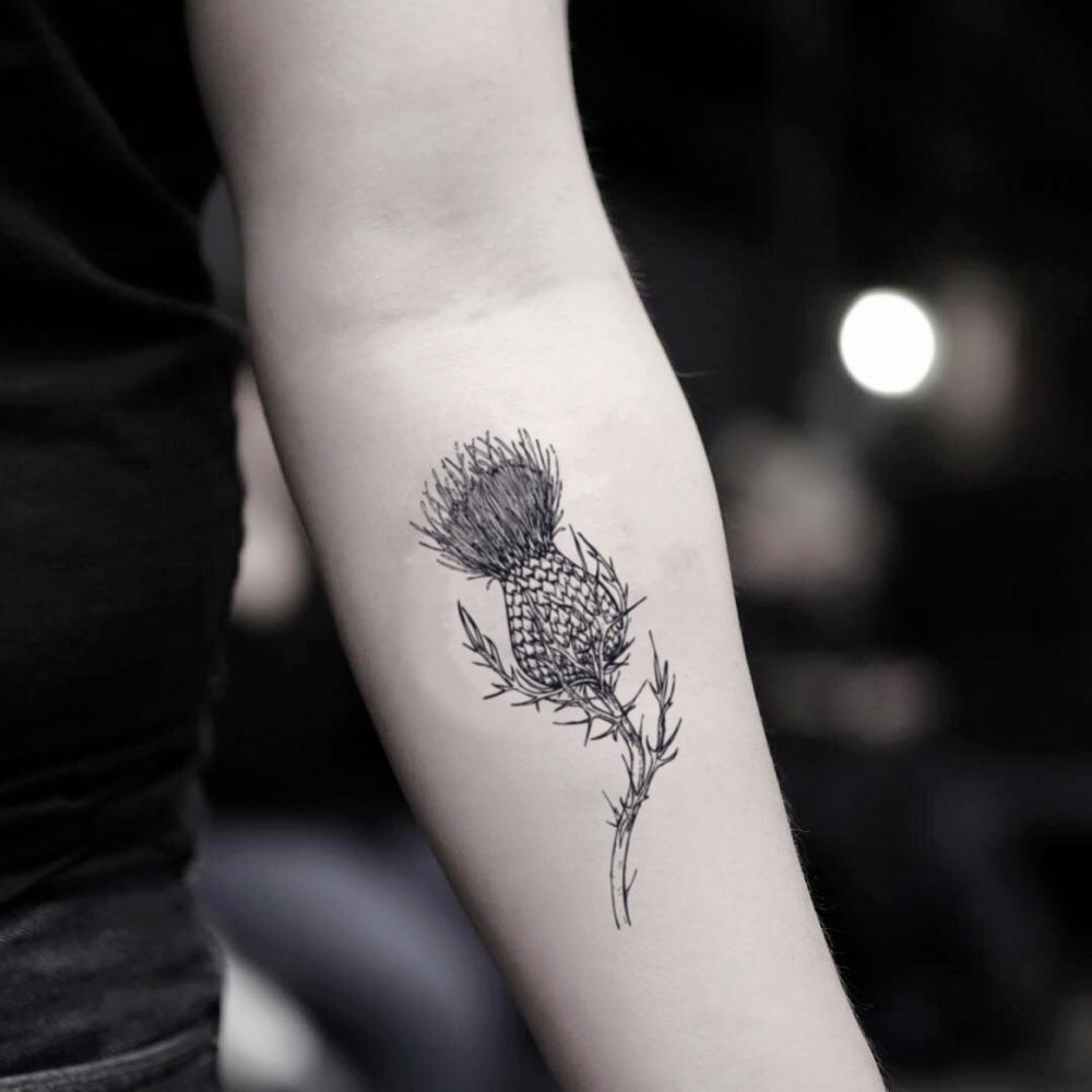 fake small thistle flower temporary tattoo sticker design idea on inner arm
