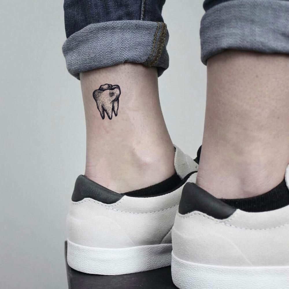fake small black tooth minimalist temporary tattoo sticker design idea on ankle
