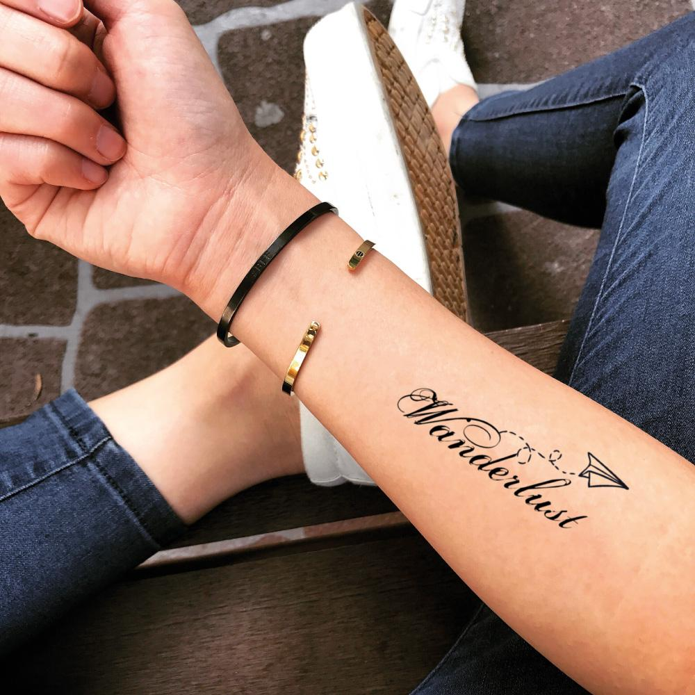 fake small wanderlust quote lettering temporary tattoo sticker design idea on forearm