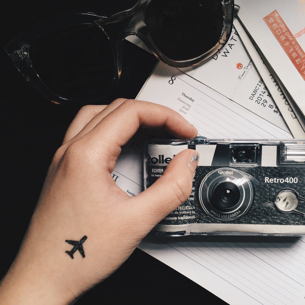 fake tiny cute little aeroplane shadow minimalist temporary tattoo sticker design idea on wrist