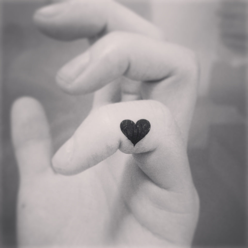 fake tiny mini black heart minimalist temporary tattoo sticker design idea on finger