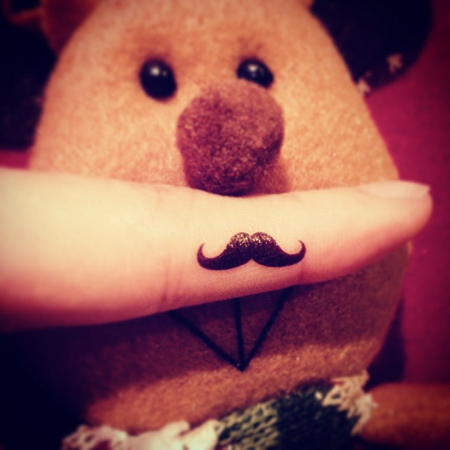 fake tiny mustache minimalist temporary tattoo sticker design idea on finger