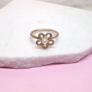 Pearl and silver lace forget me not ring displayed on marble