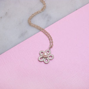 Silver lace and pearl forget me not flower necklace on pink surface