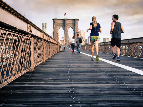 man and woman jogging on a bridge