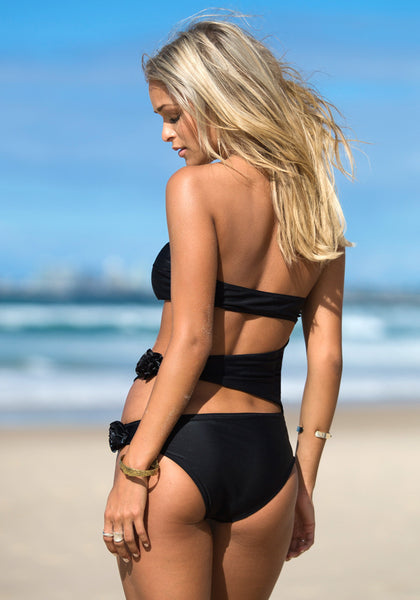 Angled back view of model in black cutout bandeau swimming suit