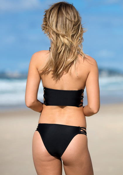 Back view of model in cutout side bikini set - black